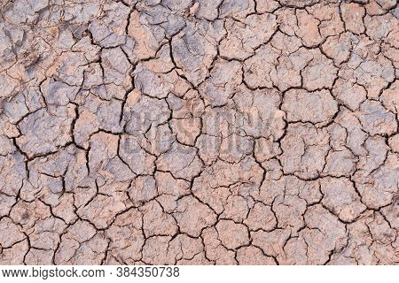 Close Up. Nature Background Of Cracked Dry Lands. Natural Texture Of Soil With Cracks. Lifeless Dese