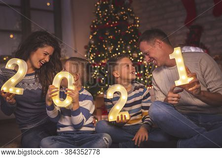 Parents Celebrating New Years Eve At Home With Kids, Sitting By The Christmas Tree, Holding Illumina