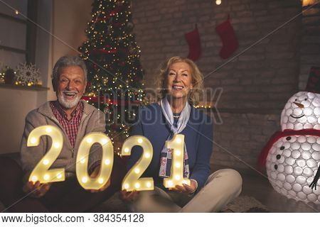 Senior Couple Sitting In Front Of Nicely Decorated Christmas Tree, Holding Illuminating Numbers 2021