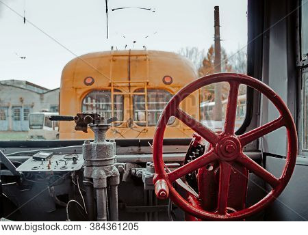 Interior Of Cabin In Historic Tram With The Controls And Levers. Another Old Streetcar Stands In The