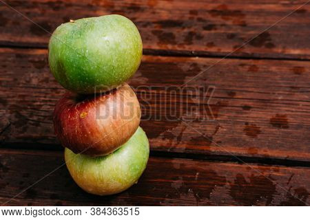 Three Apples - Green, Yellow, And Red-lie On A Wooden Table. Fresh Apples On A Wood Textured Brown B