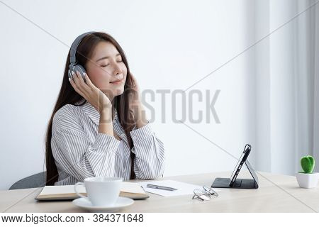 Young Asian woman happily listening to music in her private office, Relaxation by listening to music