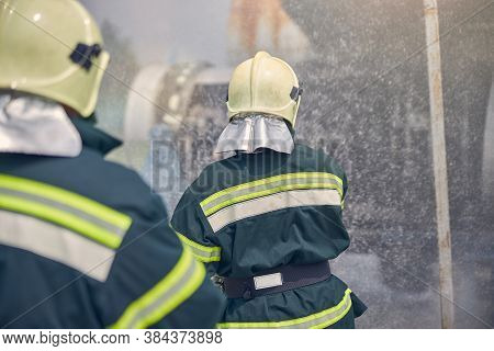 Two Firemen Wearing Fireproof Uniform Standing Next To A Emergency Place