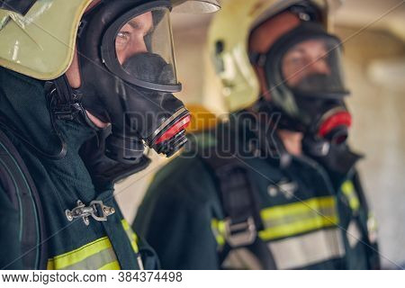 Two Firemen Wearing Protective Masks And Yellow Helmets