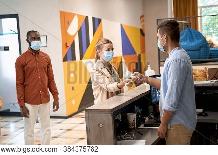 Temperature Screening, Young Man Wearing Medical Face Mask Standing At Reception And Using Infrared