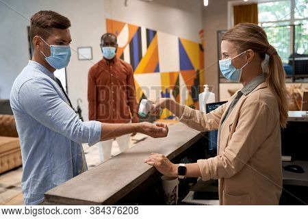 Young Woman Wearing Medical Face Mask Standing At Reception In The Office And Using Infrared Thermom