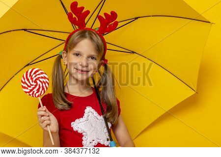 Beautiful Little Girl Wearing Costume Deer Antlers Holding A Lollipop And Yellow Umbrella Isolated O