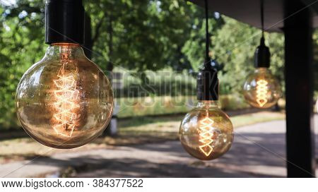 Edison Incandescent Bulbs Hang In A Retro Loft Style. Cafeteria Decoration Close-up. Street Decor Li