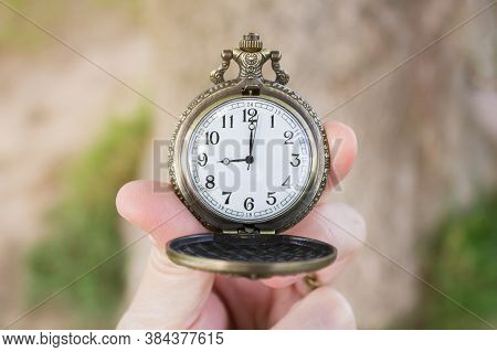 Retro Bronze Opened Pocket Watch In Human Fingers, 9 Oclock On The Dial. Close-up.