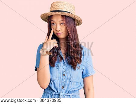 Young beautiful chinese girl wearing summer hat pointing to the eye watching you gesture, suspicious expression