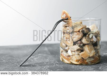 Canned Pickled Forest Mushrooms With A Fork On A Grey Table.. Glass Jar With Mushrooms Conserved For