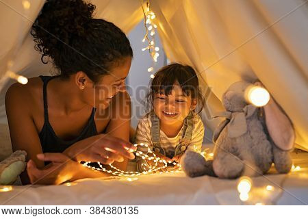 Playful mother and her daughter playing in children room in lighted tent. African mom and lovely cute girl having fun in kid hut at night at home. Mother and little daughter playing with strip lights.