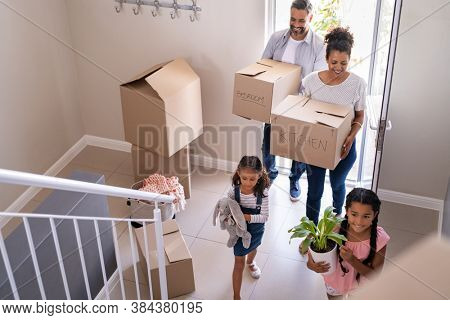 Ethnic family with two children carrying boxes and plant in new home on moving day. High angle view of happy smiling daughters helping mother and father with cardboard boxes in new house.