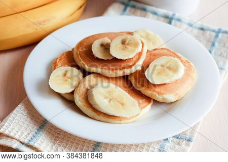 Pancakes With Sliced Banana And Cup Of Coffee On White Table
