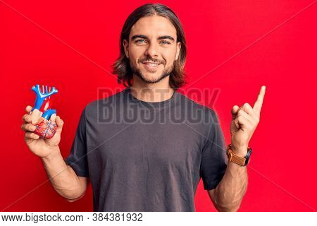 Young handsome man holding heart organ smiling happy pointing with hand and finger to the side
