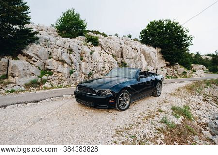 Tivat, Montenegro - 29 July 2020: A Black Ford Mustang Convertible With An Open Roof, Parked In The
