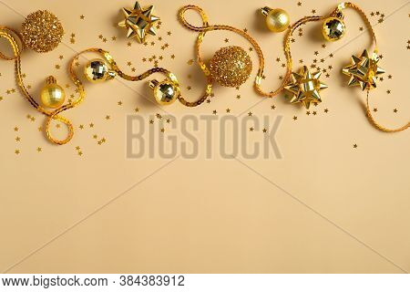 Frame Border Made Of Golden Christmas Decorations, Balls, Ribbon, Confetti On Yellow Background. Fla