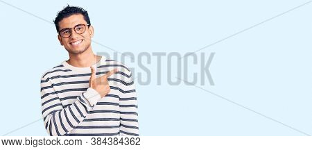 Hispanic handsome young man wearing casual clothes and glasses cheerful with a smile of face pointing with hand and finger up to the side with happy and natural expression on face