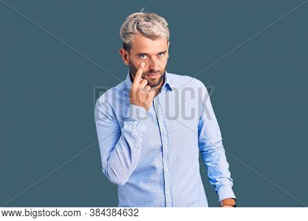 Young handsome blond man wearing elegant shirt pointing to the eye watching you gesture, suspicious expression