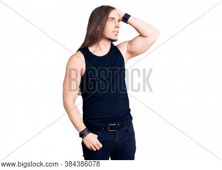 Young adult man with long hair wearing goth style with black clothes smiling confident touching hair with hand up gesture, posing attractive and fashionable