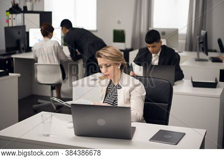 The Manager Is Busy With Office Work At A Desk In The Open-space Office Of A Large Company