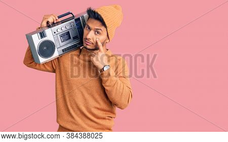 Handsome latin american young man holding boombox, listening to music pointing to the eye watching you gesture, suspicious expression