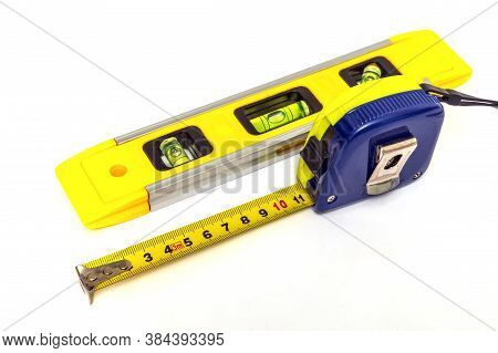 Building Level And Tape Measure For Leveling Or Measuring Objects On White Background