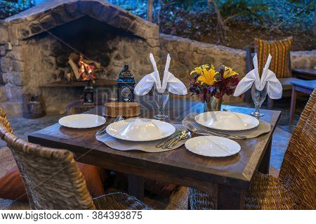 Served Table And Rattan Chairs In An Empty Restaurant Terrace Next To The Fireplace. Tanzania, Afric