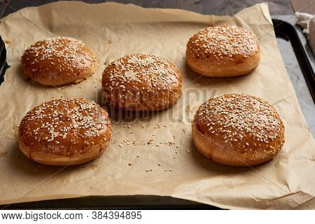 Baked Sesame Buns On Brown Parchment Paper, Ingredient For A Hamburger, Close Up