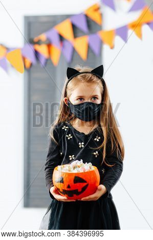 A Girl In A Halloween Costume And A Pumpkin Filled To The Brim With Treats In A Face Mask In The Cor
