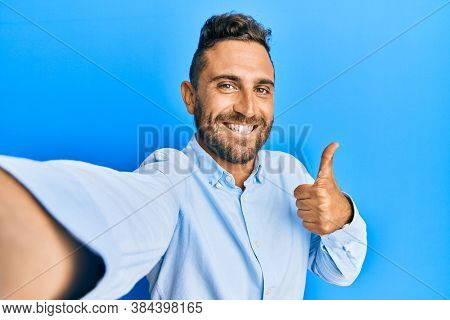 Handsome man with beard taking a selfie photo with smartphone smiling happy and positive, thumb up doing excellent and approval sign