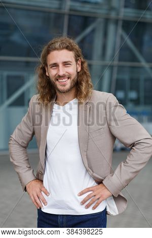 Business Portrait Of Handsome Curly Smiling Man With Long Hair In Casual Wear, Standing On City Stre