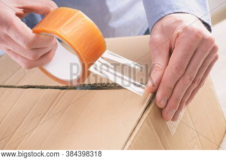 Hand holding the adhesive tape and taping the cardboard box