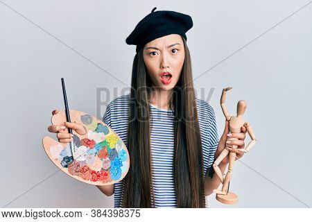 Young chinese woman wearing artist look with beret holding manikin in shock face, looking skeptical and sarcastic, surprised with open mouth