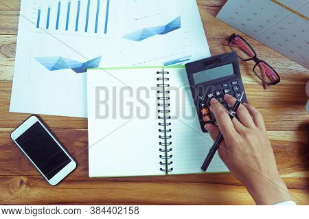 Top View Of Business People Who Use A Calculator With Financial Concepts, Spreadsheet Data, Business