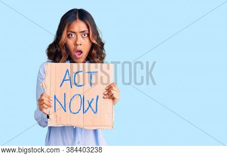 Young beautiful mixed race woman holding act now banner scared and amazed with open mouth for surprise, disbelief face