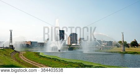 Dayton, Ohio - September 7, 2020: Skyline of Dayton, Ohio as seen through the mist of spraying fountains in morning light along Great Miami River from Deeds Point MetroPark.