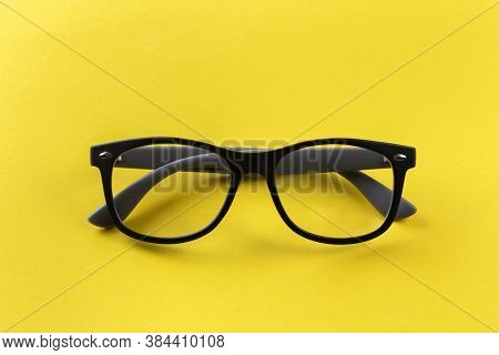 Glasses For Vision In Black Frames On A Yellow Background. Short Sighted And Presbyopia (farsightedn