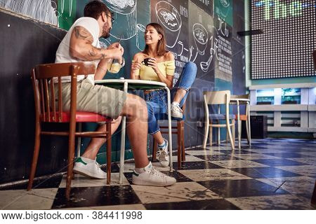 Young couple enjoying the drink and talk in a cafe