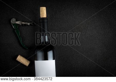 A Bottle Of Red Wine, Corkscrew And Wine Corks On Black Background, Copyspsce. Winemaking  Concept