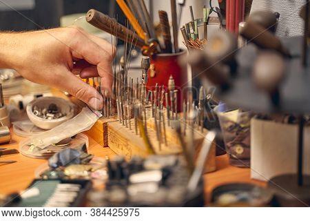 Male Hand Choosing A Bur Among The Toolkit