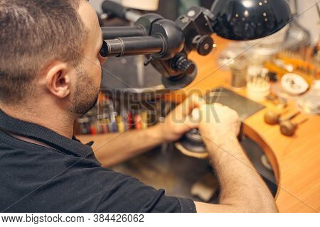 Craftsperson Using A Microscope In His Work