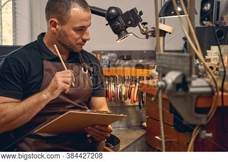 Thoughtful Jewelry Designer Sitting At The Workbench