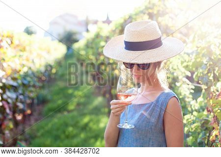 Woman Tasting Wine In Winery. Lady With Wineglass Of Pink Wine In Vineyard At Sunset. Traveler In St