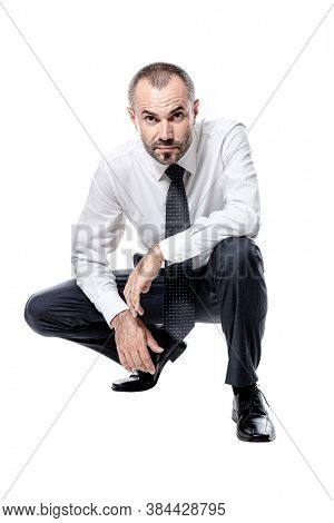 businessman crouching isolated on white. Caucasian with beard.