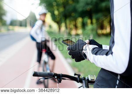 Cyclist Using Map App With Navigation On Mobile Phone. Couple Riding Bikes On Town Street. Road With