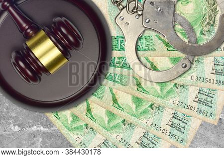 1 Brazilian Real Bills And Judge Hammer With Police Handcuffs On Court Desk. Concept Of Judicial Tri