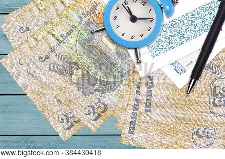 25 Egyptian Piastres Bills And Alarm Clock With Pen And Envelopes. Tax Season Concept, Payment Deadl