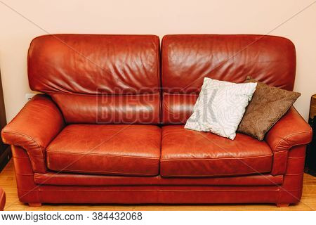 Folding Sofa Made Of Burgundy Genuine Leather With White And Brown Pillows In The Room.