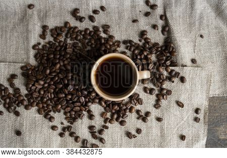 Coffee Cup With Roasted Coffee Beans On Linen Background. Mug Of Black Coffe With Scattered Coffee B